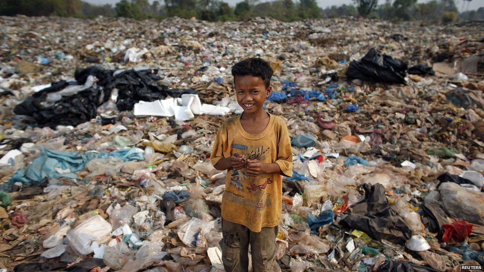 Child standing on a landfill site