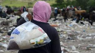 Un hombre que vive de recoger basura carga una bolsa con comida.