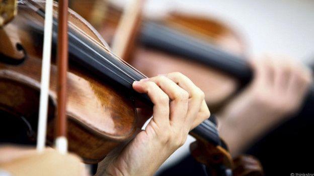 Personas tocando violines