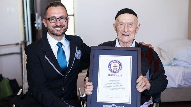 Israel Kristal sostiene la placa de reconocimiento del Récord Guinness