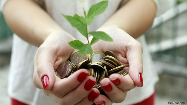 Mujer con una planta que crece del dinero