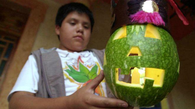 Un niño mexicano con una calabaza