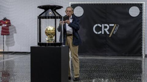 A visitor takes a photo of the Ballon D'Or at the Cristiano Ronaldo museum in Madeira
