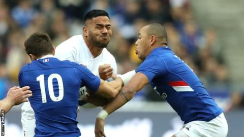 Manu Tuilagi is tackled by two French players