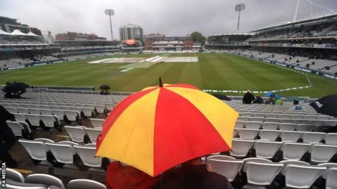 Spectator under an umbrella at Lord's