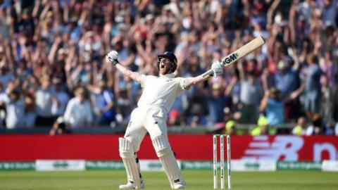 Ben Stokes roars in celebration with both arms aloft brandishing his bat