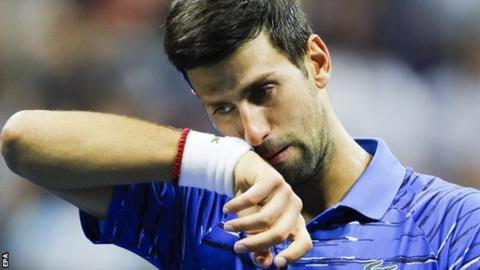 Novak Djokovic of Serbia walks back to the baseline before retiring due to injury against Stan Wawrinka of Switzerland during a match on the seventh day of the US Open Tennis Championships