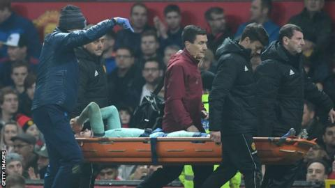 Arsenal's Rob Holding is taken off on a stretcher