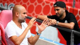 Pep Guardiola speaks to Riyad Mahrez before Sunday's Community Shield