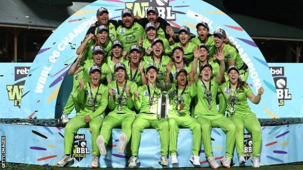 Sydney Thunder players and staff celebrate with the WBBL trophy after beating Melbourne Stars in the final