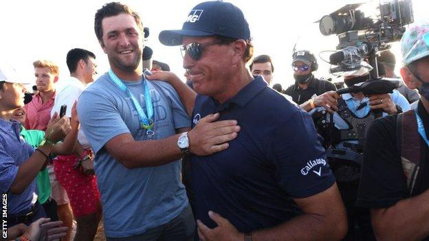 Jon Rahm congratulates Phil Mickelson on his victory