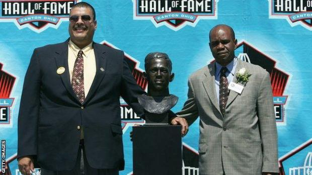 Grandchildren Fritz III (left) and Steven Towns (right) pose with a bust of Pollard at his 2005 Hall of Fame induction