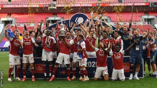 Arsenal players celebrate with the FA Cup trophy after beating Chelsea behind closed doors in the 2020 final at Wembley stadium