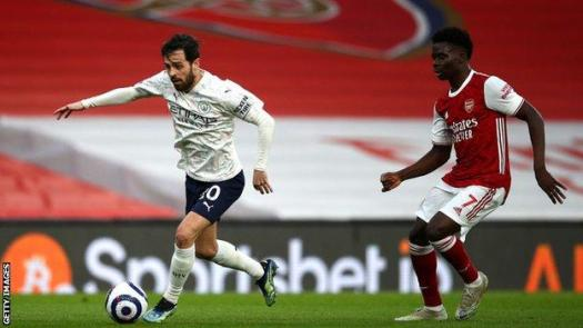 Bernardo Silva of Manchester City gets past Bukayo Saka of Arsenal on Sunday