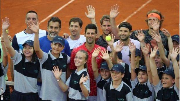 Novak Djokovic with players and ballboys and girls