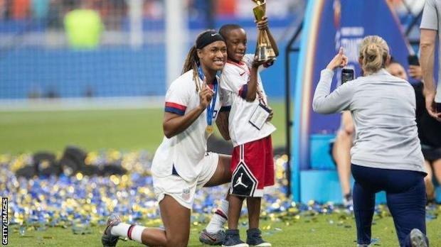 Jessica McDonald with her son Jeremiah as he holds the Women's World Cup trophy