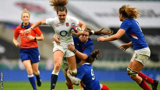 Two French players try to tackle Ellie Kildunne