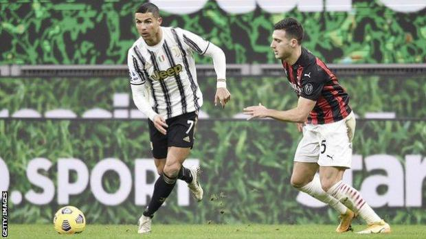 Juventus forward Cristiano Ronaldo (left) dribbles past AC Milan player Diogo Dalot (right)