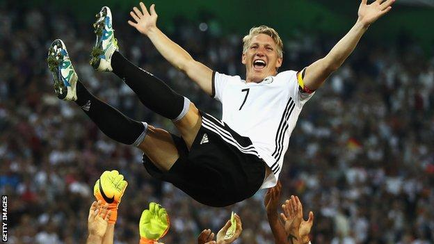 Schweinsteiger is thrown into the air by his Germany team-mates after his final match