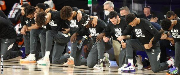 Utah Jazz and New Orleans Pelicans players kneel before their game