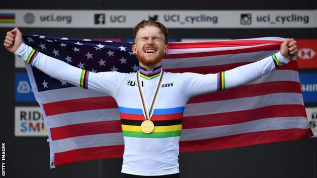 Quinn Simmons holds up the US flag on the podium after winning the road race at the World Junior Championships in 2019