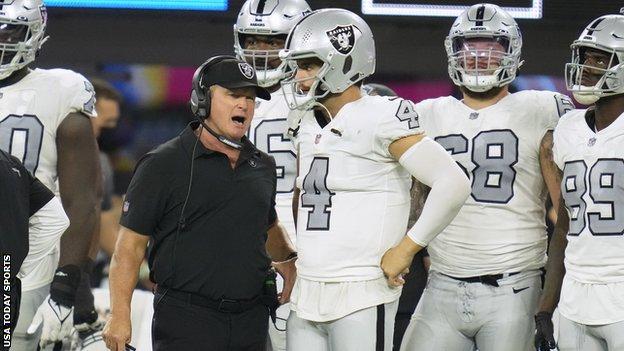 Jon Gruden speaks with Las Vegas Raiders quarterback Derek Carr