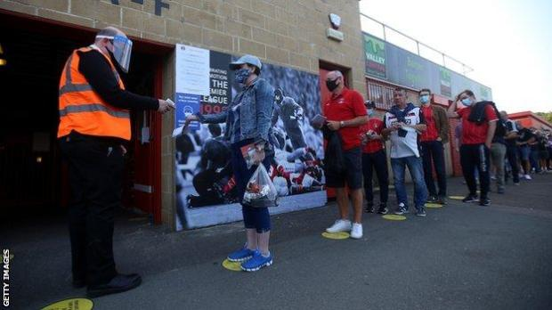 Fans queue socially distanced to enter a League One match between Charlton and Doncaster