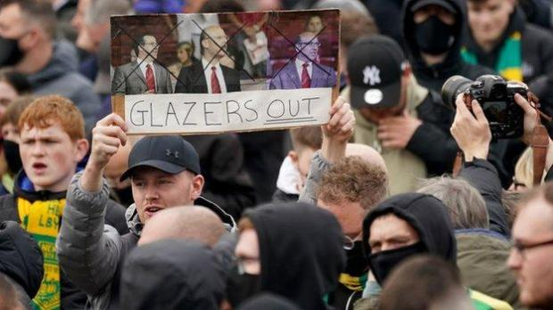 A Manchester United fan holds an anti-Glazer poster in the air