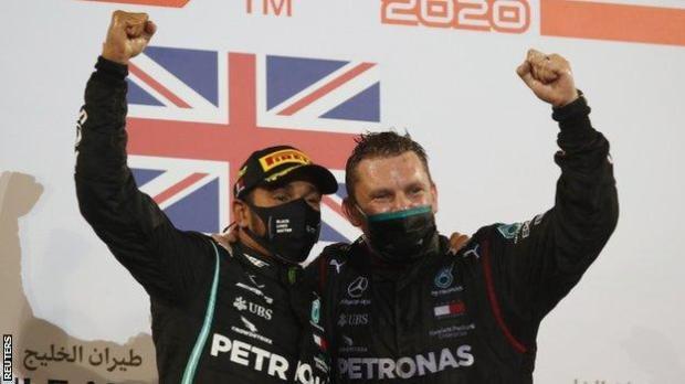 Lewis Hamilton celebrates on the podium with a Mercedes team member