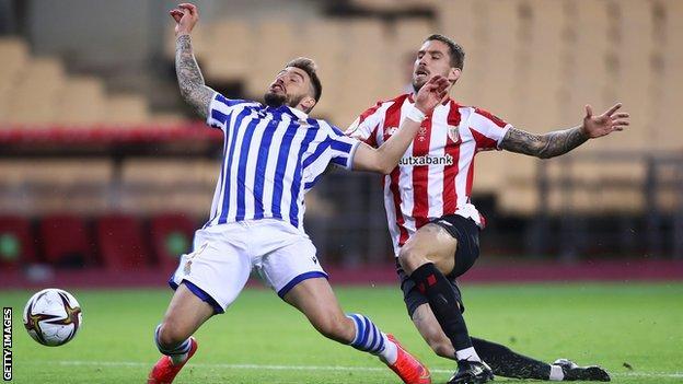 Inigo Martinez of Athletic Bilbao fouls Real Sociedad's Portu