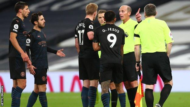 Tottenham players protesting with referee Mike Dean