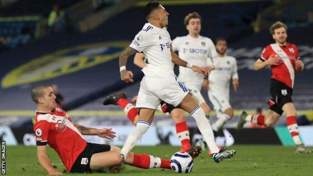 Oriol Romeu slides in to tackle Raphinha in the box