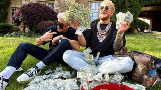 Jake Paul holds dollar bills and some lie on the floor around him