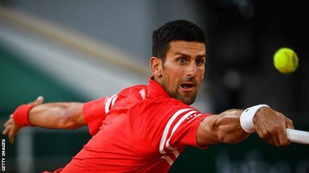 Novak Djokovic returns a ball against Tennys Sandgren in the French Open