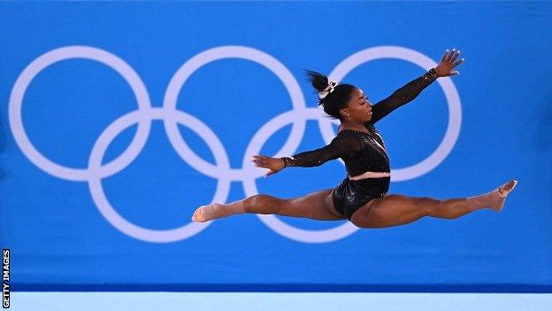 Simone Biles training in front of Olympic rings