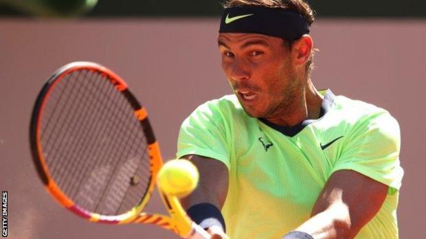 Rafael Nadal returns in his French Open match against Alexei Popyrin