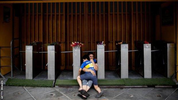 A mother and son mourn Maradona outside La Bombonera