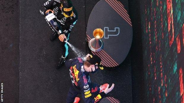 Lewis Hamilton sprays Max Verstappen with champagne