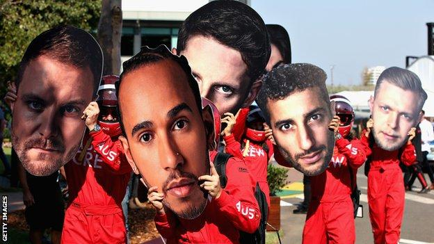 Albert Park workers hold giant cardboard cutouts of F1 drivers' faces