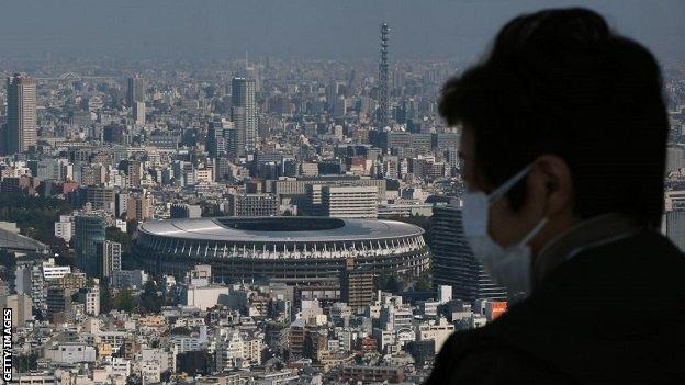 A masked spectator overlooks the Tokyo skyline, which features the Olympic Stadium