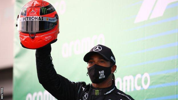 Lewis Hamilton holds up Michael Schumacher's race helmet