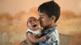 Elison, de dos meses, en brazos de su hermano José Wesley, de 10 años, en su casa de Poco Fundo, Pernambuco