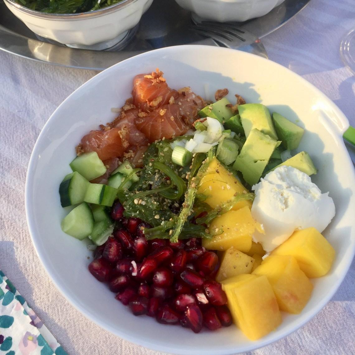 Poke bowl de poisson mariné avec saumon mariné concombre avocat mangue grenade, wakamé et un peu de fromage frais