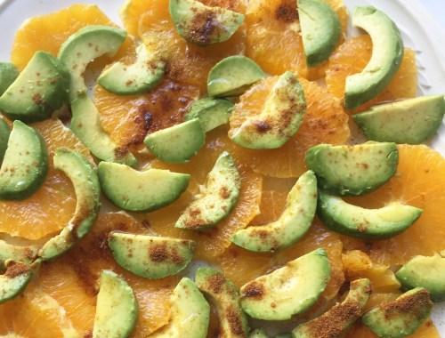 Salade d'oranges coupées en rondelles et quartiers d'avocat, arrosée d' huile de noisette et saupoudrée de paprika