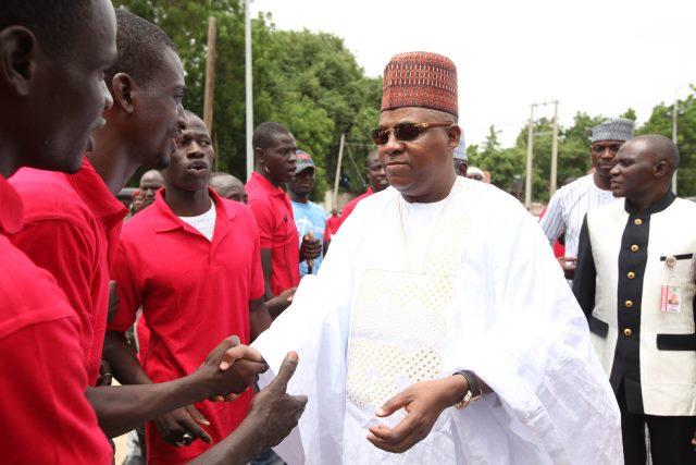 Borno State Governor, Kashim Shettima shaking hands with Civilian JTF members in Maiduguri. (AP Photo/Sunday Alamba)