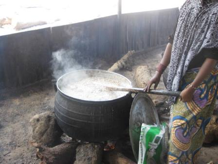 A cook mixing food on fire at Dalori Camp