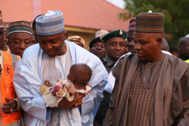 Saraki carrying a recovering baby at a health facility in Borno State, as the State Governor, Kashim Shettima looks on