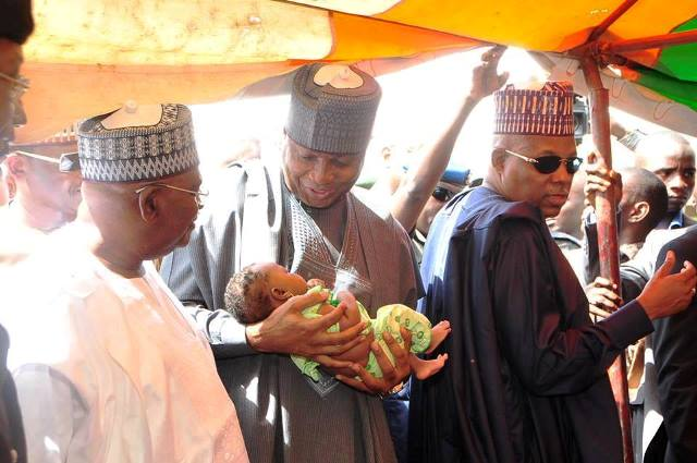 Bukola Saraki cuddles a baby during one of his visits to an IDP camp in Maiduguri