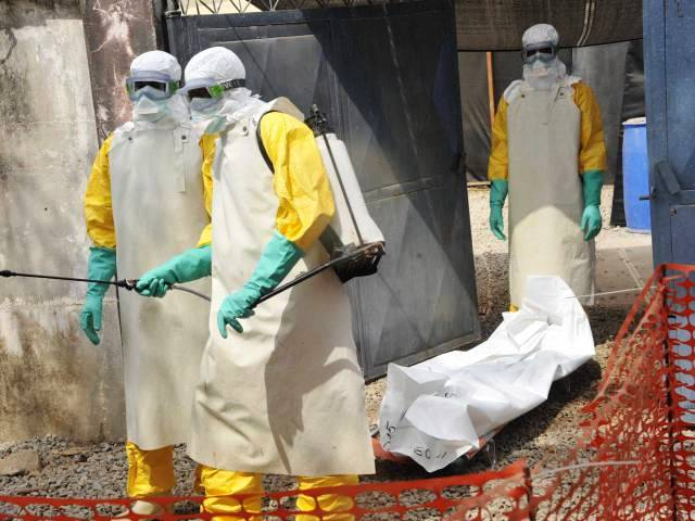 TOPSHOTS Members of the Guinean Red Cross move the body of a person who died from the Ebola virus on March 8, 2015 at the Donka hospital in Conakry. More than 9,700 people have died of the disease since the west African epidemic emerged in southern Guinea in December 2013, with nearly 24,000 people infected, according to the World Health Organization. AFP PHOTO / CELLOU BINANICELLOU BINANI/AFP/Getty Images