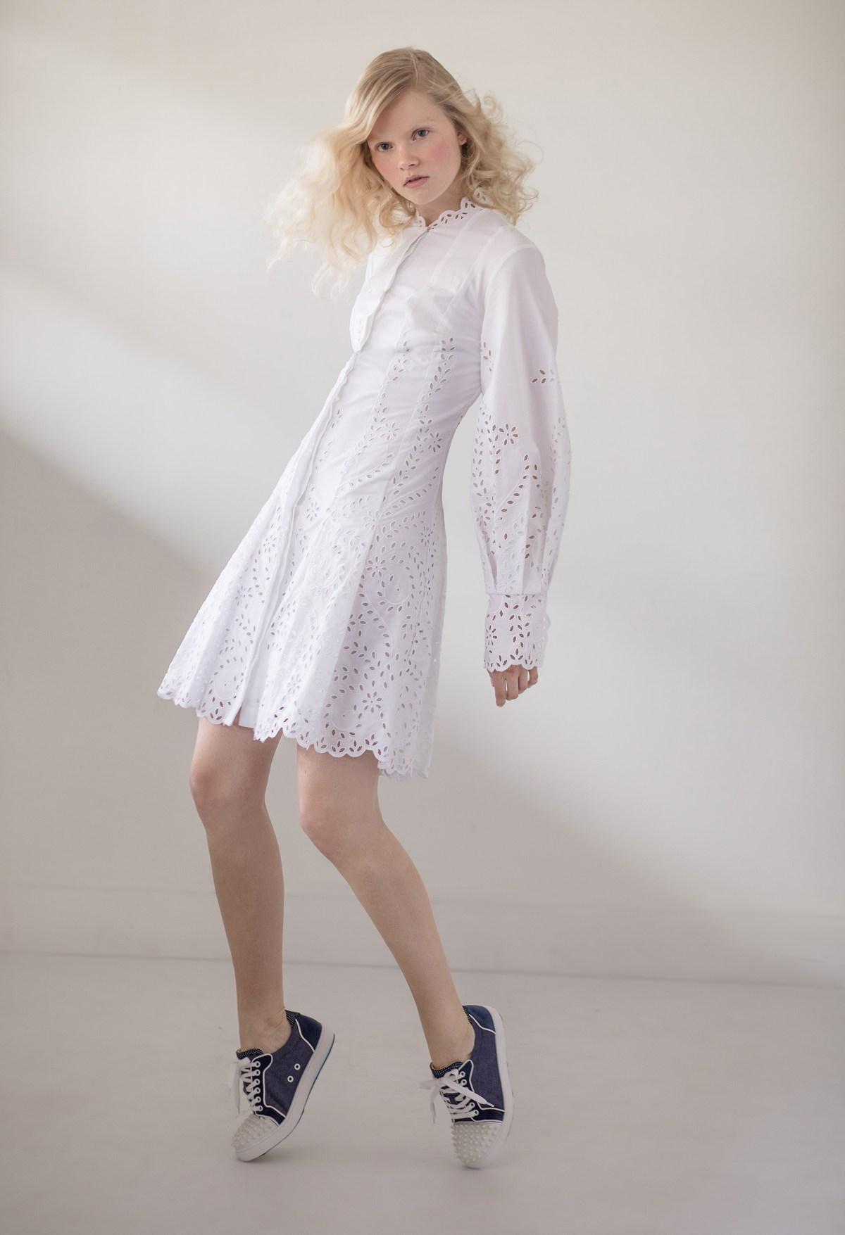 Blond model wearing a white Oscar de la Renta dress and Christian Louboutin shoes